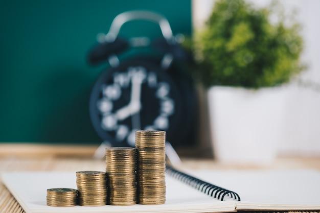 Pilhas de moedas e despertador com lousa verde, Foto Premium