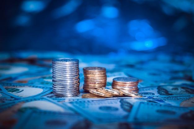 Pilhas de moedas no fundo de cem notas de dólar. luz azul escuro. Foto Premium
