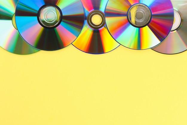 Pilhas de velhos cds, dvd em fundo pastel. o disco usado e empoeirado com espaço da cópia para adiciona o texto. Foto Premium