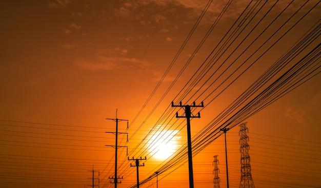 Pilões da eletricidade da silhueta durante o por do sol. poder e energia. conservação de energia. Foto Premium