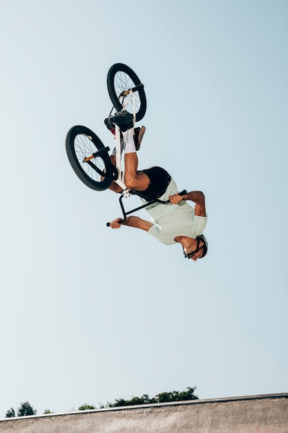 Piloto de bicicleta extrema realizando saltos perigosos Foto gratuita