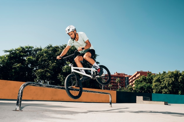 Piloto de bmx, executando truques no skatepark Foto gratuita