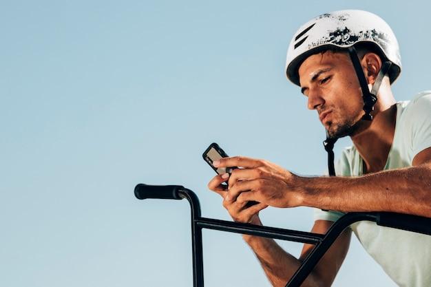 Piloto de bmx, olhando para o telefone tiro médio Foto gratuita