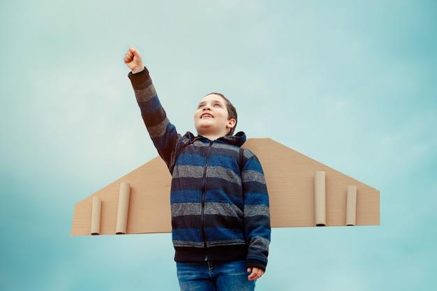 Piloto de criança com asas de papel jogando avião e sonhos de viagens aéreas Foto Premium