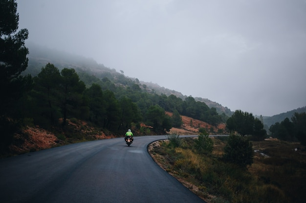 Piloto de motocicleta em estrada rural vazia Foto gratuita