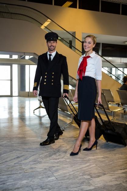 Piloto e aeromoça caminhando com seus tróleis Foto gratuita