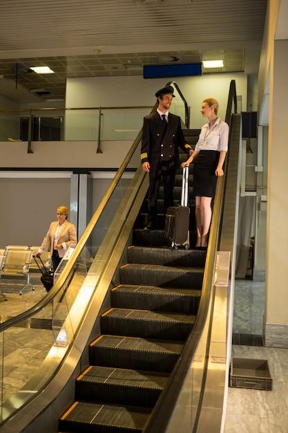 Piloto e equipe conversando na escada rolante Foto gratuita