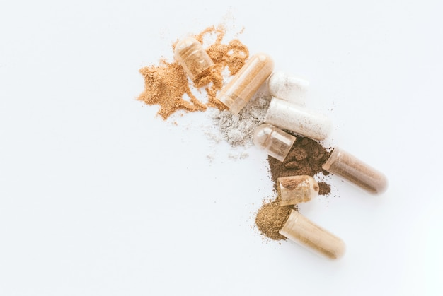 Pílulas à base de plantas. abra cápsulas e pó ervais no fundo branco. copyspace Foto Premium