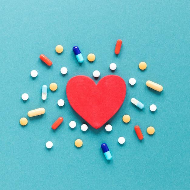 Pílulas coloridas de vista superior com coração em cima da mesa Foto gratuita