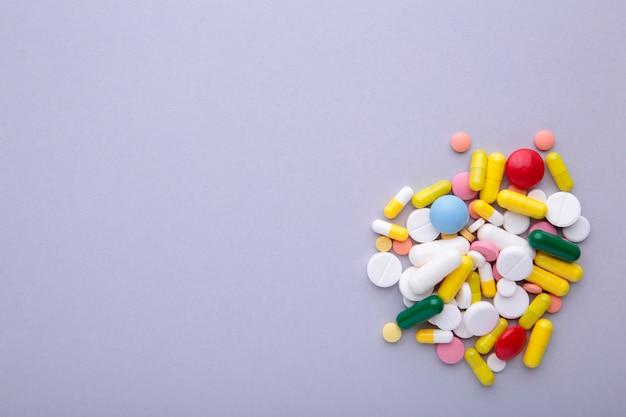 Pílulas coloridas e comprimidos em cinza Foto Premium