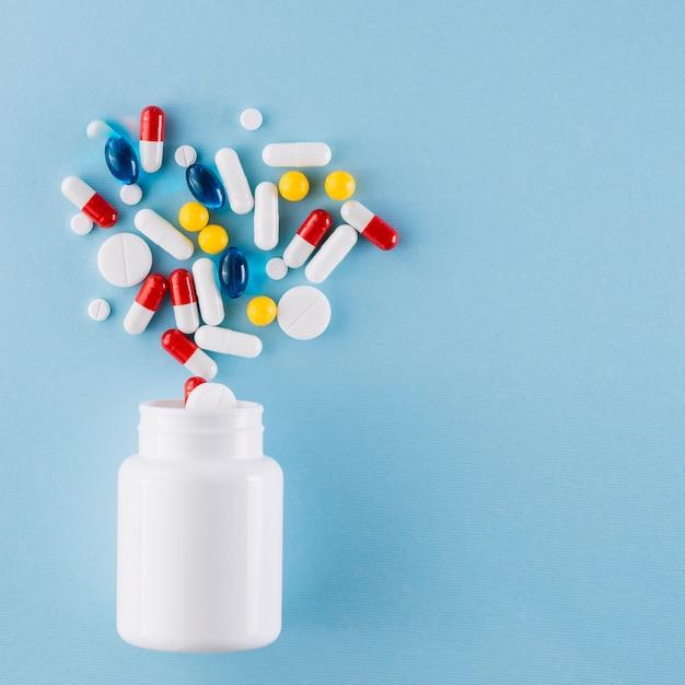 Pílulas coloridas e garrafa de plástico Foto gratuita