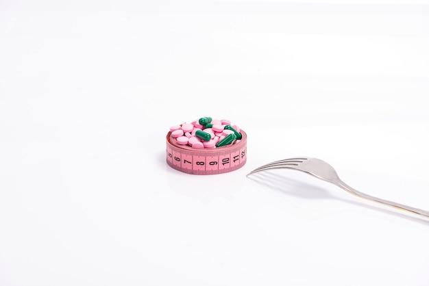 Pílulas de dieta multicoloridas e suplementos, como alimentos em um prato na forma de uma fita de centímetro com um garfo Foto Premium