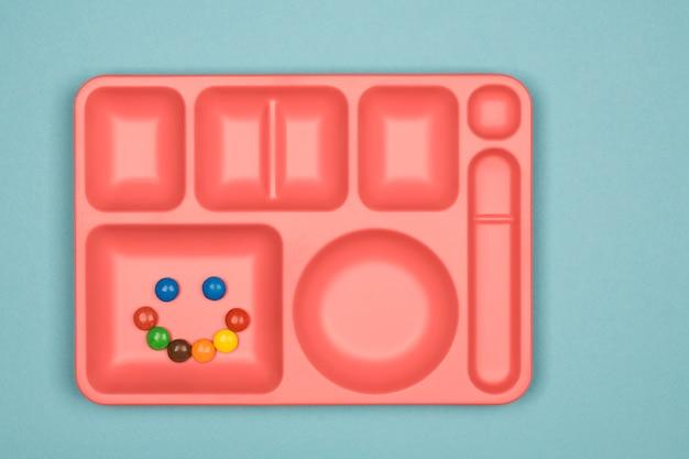 Pílulas de doces de chocolate coloridos na bandeja sobre fundo azul Foto Premium