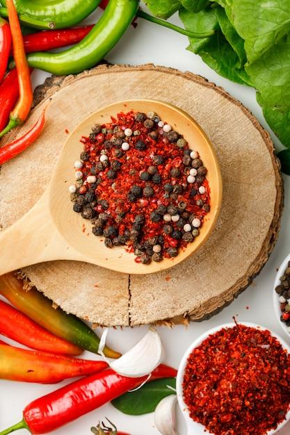 Pimenta com alho, pimenta, pimenta caiena, hortaliças e placa de madeira em branco Foto gratuita