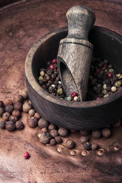 Pimenta em um almofariz de madeira com uma colher Foto Premium