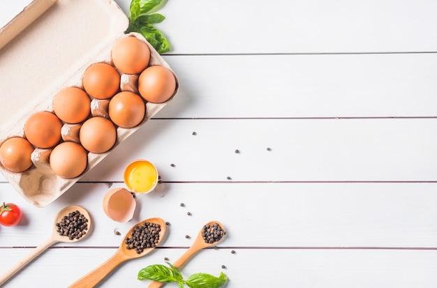 Pimenta na colher de pau com folhas de manjericão e ovos na caixa Foto gratuita