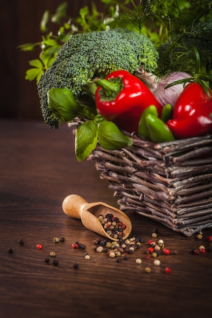 Pimenta na madeira com legumes na cesta Foto gratuita