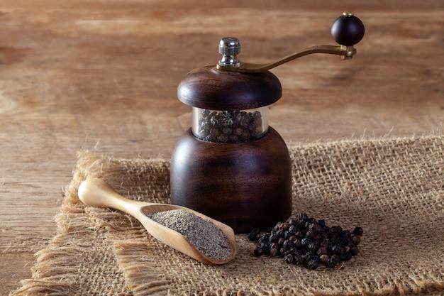 Pimenta preta e moedor de pimenta no chão de madeira Foto Premium