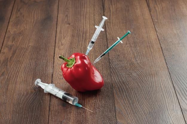 Pimenta vermelha e preso nele uma seringa em um fundo de madeira Foto Premium