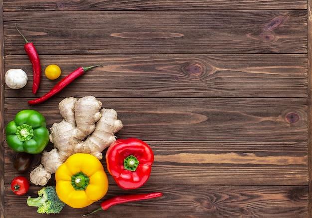 Pimentão vermelho, verde e amarelo, gengibre e tomate cereja em fundo de madeira Foto Premium