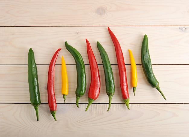 Pimentas estão em uma fileira com pimenta amarela, verde e vermelha Foto Premium