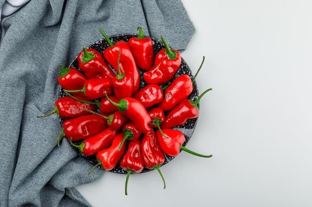 Pimentas vermelhas em um prato na parede branca e têxtil, vista superior. Foto gratuita