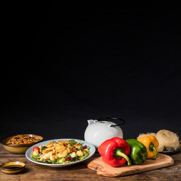 Pimentões; bule de chá; molho de soja e macarrão na mesa de madeira contra o fundo preto Foto gratuita