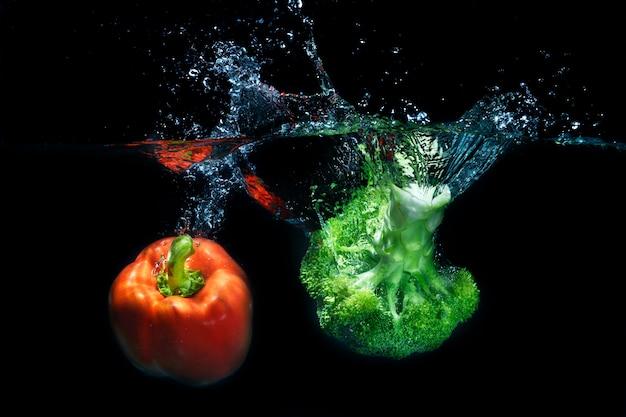 Pimentões e vegetais frescos da paprika que espirram no respingo claro da água Foto Premium