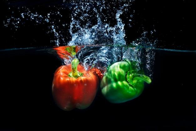 Pimentões frescos da paprika que espirram no respingo claro da água Foto Premium