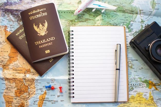 Pin no mapa de localização para o plano de viagem com a câmera bússola de passaporte e notebook. Foto Premium