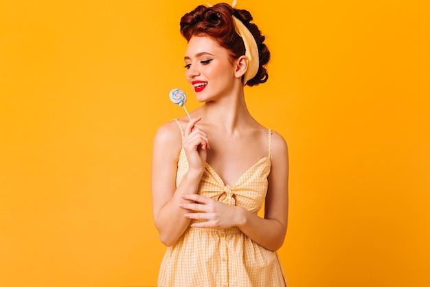 Pin-up encantadora segurando rebuçados. foto de estúdio de mulher pensativa de gengibre com pirulito isolado no espaço amarelo. Foto gratuita