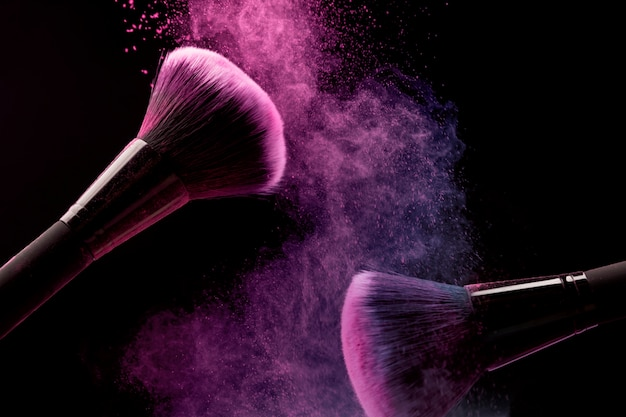 Pincéis cosméticos e pó de maquiagem em fundo escuro Foto gratuita