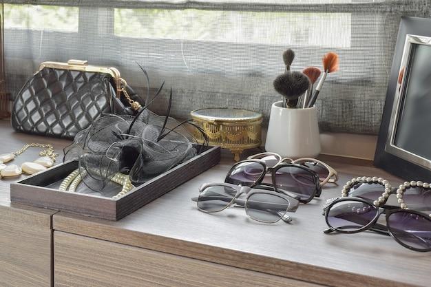Pincéis de bolsa, óculos de sol, jóias e maquiagem em uma penteadeira de madeira Foto Premium