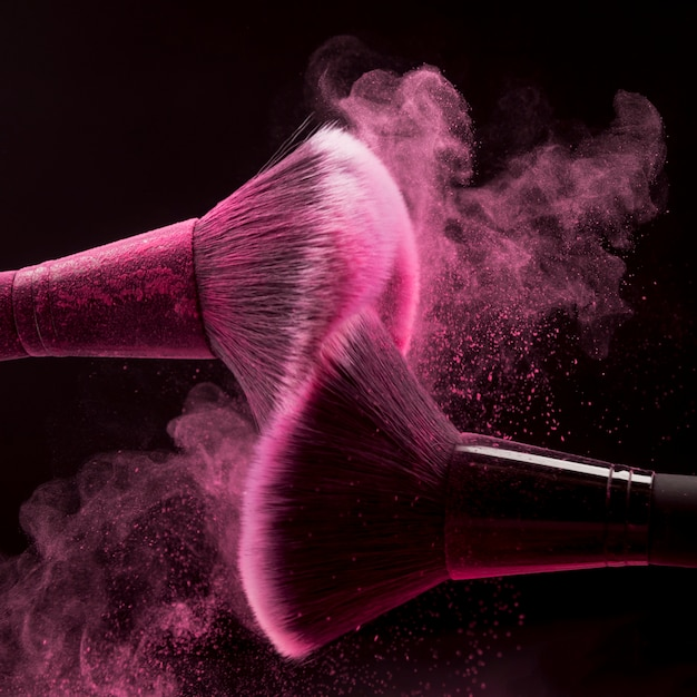 Pincéis de maquiagem com respingo de pó-de-rosa Foto gratuita