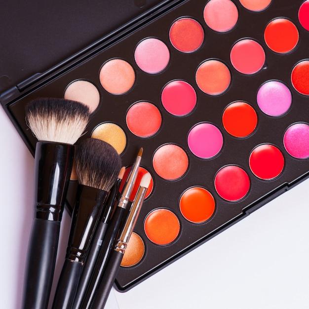 Pincéis de maquiagem no suporte e cosméticos isolados no branco Foto Premium