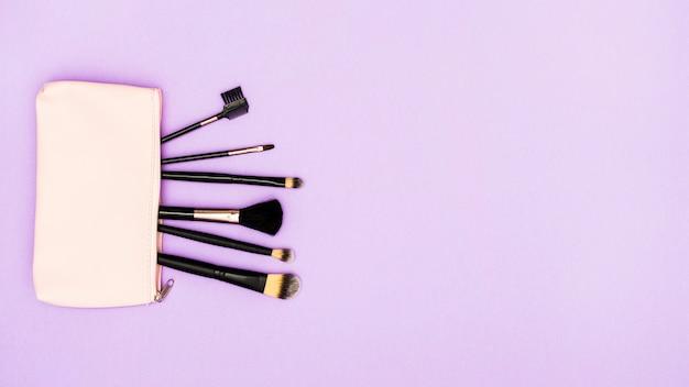 Pincéis de maquiagem preta no saco bege no fundo roxo Foto gratuita