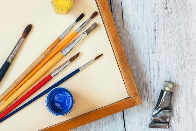 Pincéis e tintas coloridas em latas estão em uma mesa de madeira Foto Premium