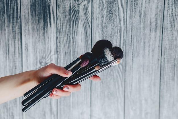 Pincéis para maquiagem nas mãos em fundo de madeira Foto Premium