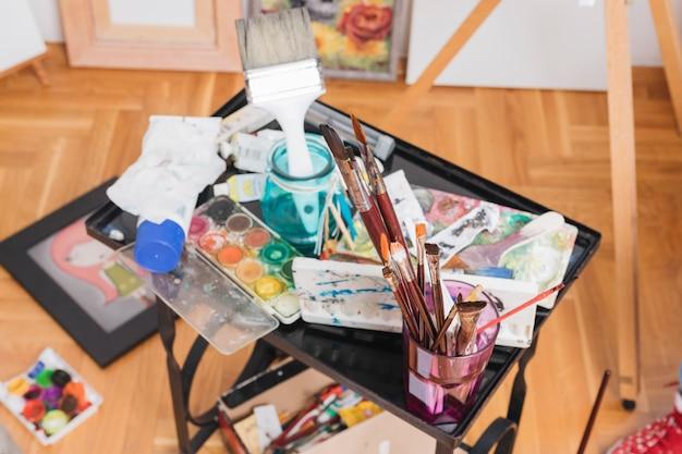 Pincéis usados e tintas abertas colocadas na mesa preta Foto gratuita