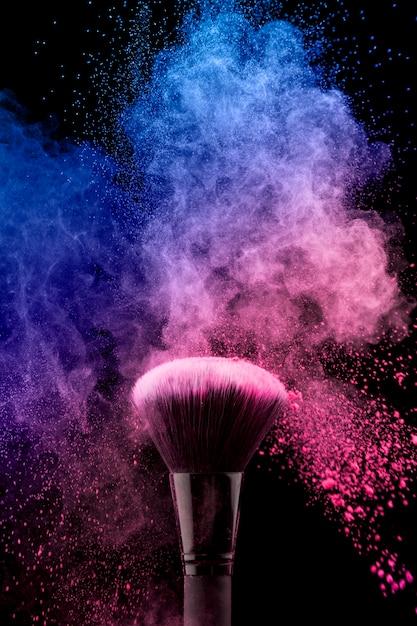 Pincel de maquiagem com pó rosa colorido Foto gratuita
