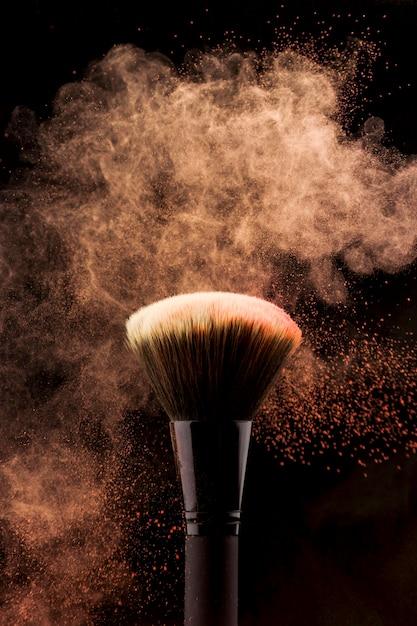 Pincel de maquiagem com respingo de pó de cor pêssego Foto gratuita