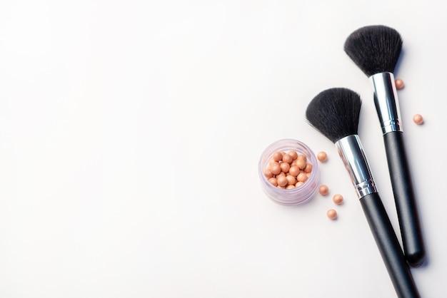 Pincel de maquiagem e blush em um fundo branco. conceito de beleza. close-up com espaço para texto Foto Premium