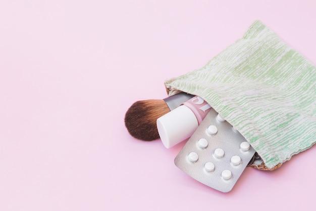 Pincel de maquiagem; frasco de verniz de unhas e blister pílula branca dentro da bolsa de algodão sobre fundo rosa Foto gratuita