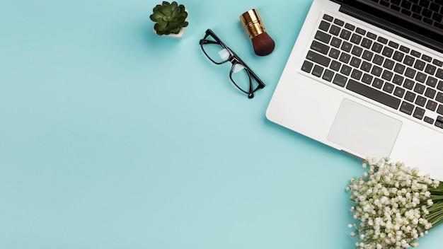 Pincel de maquiagem, óculos, cacto planta buquê de flores brancas com laptop sobre fundo azul Foto gratuita