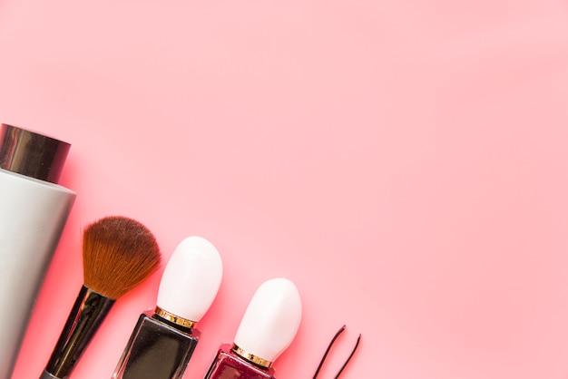 Pincel de maquiagem; produto de cosméticos e pinças no pano de fundo rosa Foto gratuita