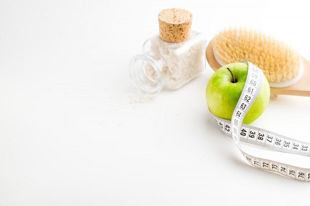 Pincel de massagem a seco com fita métrica. única maçã verde e garrafa de vidro com sal do mar na mesa branca. saúde e dieta. Foto Premium