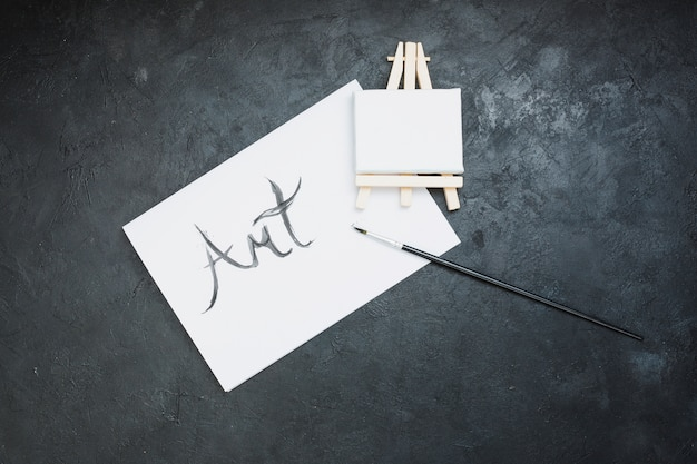 Pincel; mini cavalete e papel de texto de arte em fundo preto Foto gratuita