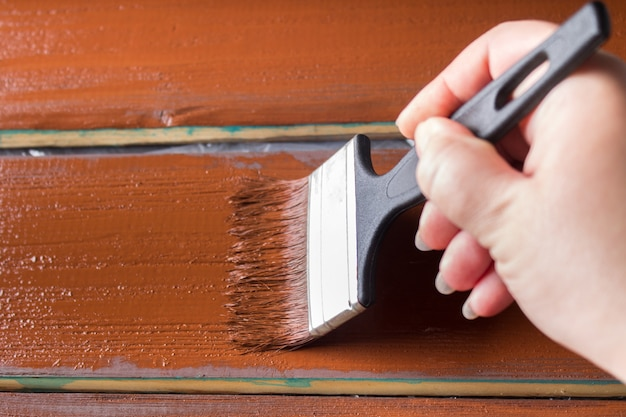 Pincele com tinta na mão. um homem pinta placas azuis em um pincel marrom. Foto Premium