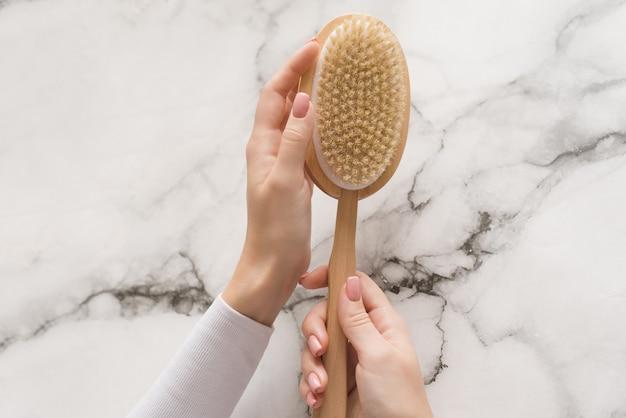 Pincele para massagem seca nas mãos de uma menina em um fundo de mármore. escova para esfregar o corpo, colocando-o em ordem, contra celulite e casca de laranja Foto Premium