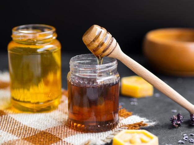 Pingando mel em frasco de vidro Foto gratuita